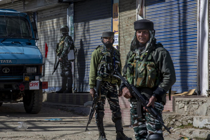 Indian paramilitary soldiers stand guard during a gunbattle between Indian soldiers and suspected militants in Shopian, south of Srinagar, Indian controlled Kashmir, Friday, April 9, 2021. Seven suspected militants were killed and four soldiers wounded in two separate gunfights in Indian-controlled Kashmir, officials said Friday, triggering anti-India protests and clashes in the disputed region. (AP Photo/ Dar Yasin)