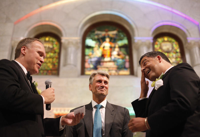 Al Giraud, right, wipes a tear from his eye as his partner Jeff Isaacson, left. reads his wedding vows as Mayor R.T. Rybak officiates their ceremony at the Minneapolis Freedom to Marry Celebration and Weddings at Minneapolis City Hall, Thursday, Aug. 1, 2013. They were the first gay couple legally married in Minnesota. (AP Photo/Stacy Bengs)