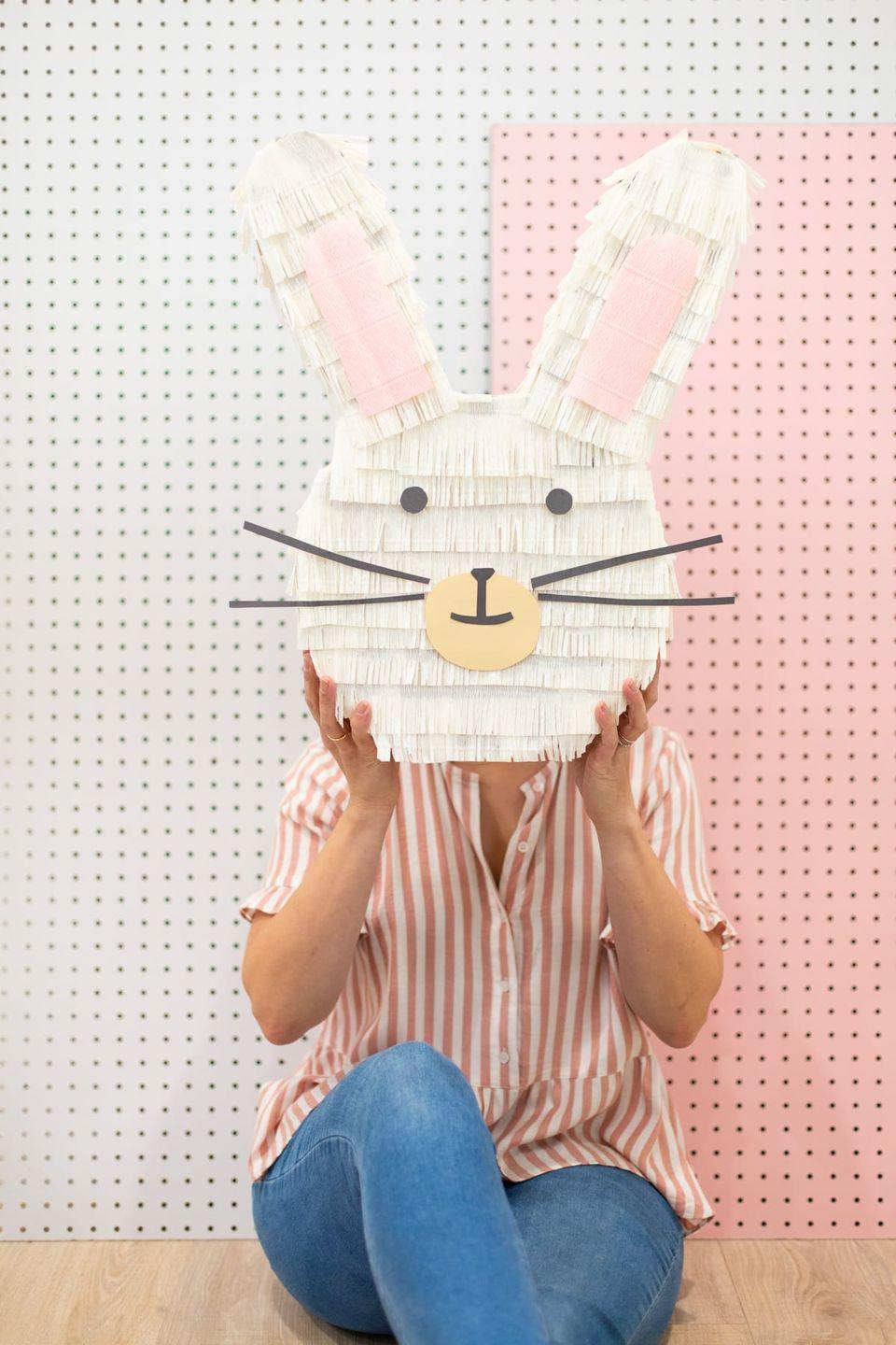 """<p>With a little cardboard and a little creativity, you can make an adorable bunny piñata that will be the life of the party – especially if you've got kids. Make sure you fill it with some incredible <a href=""""https://www.goodhousekeeping.com/holidays/easter-ideas/g2367/easter-candies/"""" rel=""""nofollow noopener"""" target=""""_blank"""" data-ylk=""""slk:Easter candies"""" class=""""link rapid-noclick-resp"""">Easter candies</a>. </p><p><em><a href=""""https://lovelyindeed.com/how-to-make-a-bunny-pinata/"""" rel=""""nofollow noopener"""" target=""""_blank"""" data-ylk=""""slk:Get the tutorial at Lovely Indeed »"""" class=""""link rapid-noclick-resp"""">Get the tutorial at Lovely Indeed »</a> </em></p><p><strong>RELATED:</strong> <a href=""""https://www.goodhousekeeping.com/holidays/easter-ideas/g4154/easter-games/"""" rel=""""nofollow noopener"""" target=""""_blank"""" data-ylk=""""slk:20 Fun Easter Games for Kids to Play All Day"""" class=""""link rapid-noclick-resp"""">20 Fun Easter Games for Kids to Play All Day</a></p>"""
