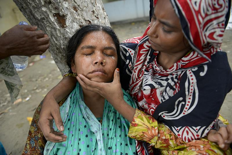 A woman faints after weeping for hours near the rubble of the eight-story Rana Plaza building that collapsed in Savar, near Dhaka, Thursday, May 9, 2013. The death toll from the collapse of the garment factory building passed 900 on Thursday even as a fire in an 11-story garment factory Wednesday night in Dhaka killed eight people, including a ruling-party politician and a top official in the country's powerful clothing manufacturers' trade group. (AP Photo/Ismail Ferdous)
