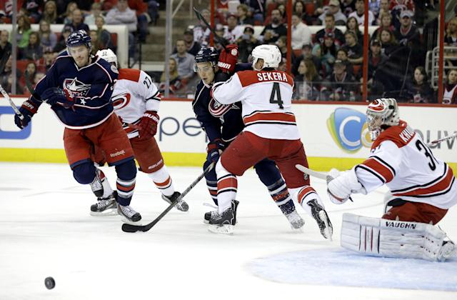 Carolina Hurricanes goalie Anton Khudobin, of Kazakhstan, and Andrej Sekera (4), of Slovakia, defend the goal against Columbus Blue Jackets' Boone Jenner (38) and Corey Tropp (26) during the first period of an NHL hockey game in Raleigh, N.C., Saturday, March 29, 2014. (AP Photo/Gerry Broome)
