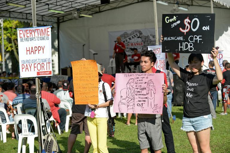 Protesters display placards during a rally at speakers corner in Singapore on October 5, 2013