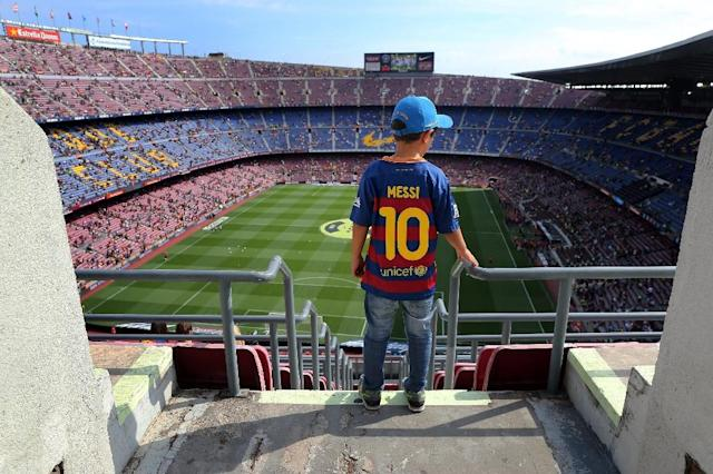 A boy wearing a jersey of Lionel Messi looks at the Camp Nou stadium on September 26, 2015 (AFP Photo/Cesar Manso)