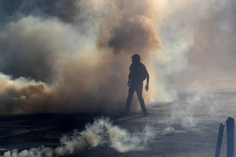 A protester stands amid tear gas fired by police trying to disperse an anti-government demonstration in Santiago, Chile, Friday, Dec. 27, 2019. Chile has been roiled by continuing and sometimes violent street protests since Oct. 18, when a student protest over a modest increase in subway fares turned into a much larger and broader movement with a long list of demands that largely focus on inequality. (AP Photo/Fernando Llano)