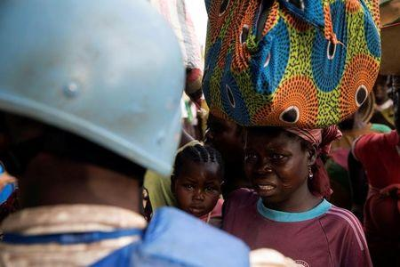 A Cameroonian United Nations peacekeeper talks to women fleeing the village of Zike as they arrive to the village of Bambara