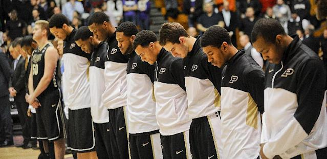 Members of the Purdue mens basketball team pause for a moment of silence before their NCAA college basketball game against Northwestern in Evanston, Ill., on Tuesday, Jan. 21, 2014. Their was shooting on their campus earlier in the day. (AP Photo/Matt Marton)