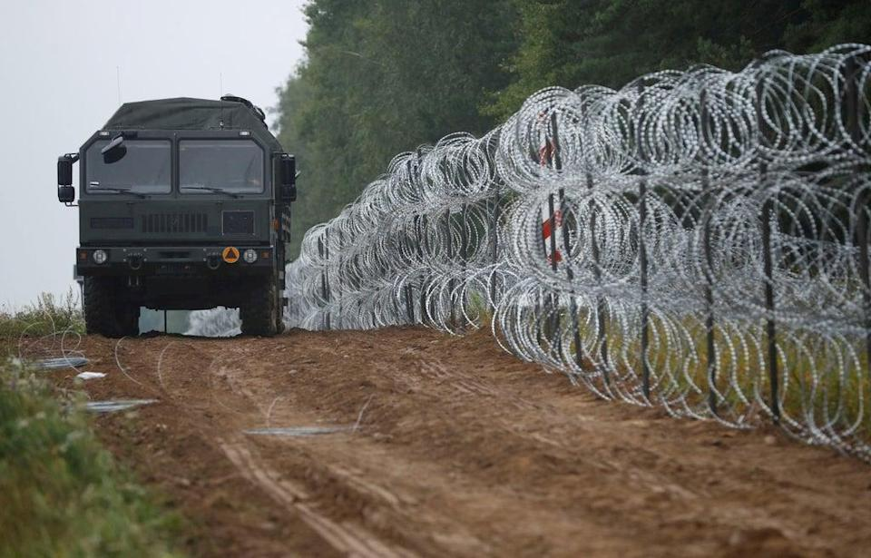 A view of a vehicle next to a fence built by Polish soldiers on the border between Poland and Belarus (REUTERS)