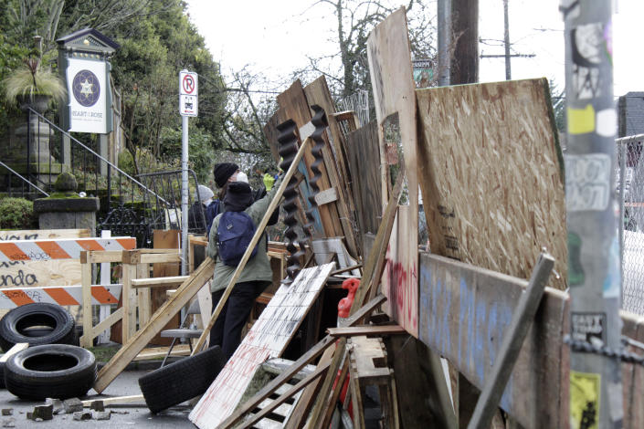 Protesters reinforce their barricades at an encampment outside a home in Portland, Ore., on Wednesday, Dec. 9, 2020. Makeshift barricades erected by protesters are still up in Oregon's largest city a day after Portland police arrested about a dozen people in a clash over gentrification and the eviction of a family from a home. (AP Photo/Gillian Flaccus)