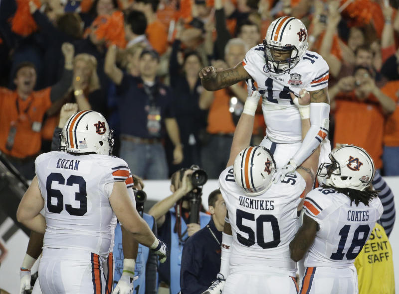 Auburn quarterback Nick Marshall is lifted by teammates after rushing for a touchdown during the first half of the NCAA BCS National Championship college football game against Florida State Monday, Jan. 6, 2014, in Pasadena, Calif. (AP Photo/Chris Carlson)