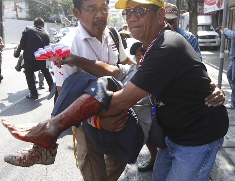 An anti-government protester injured in an explosion is carried by his fellow protesters during a demonstration in Bangkok, Thailand, Friday, Jan. 17, 2014. Dozens of people were wounded when an explosion hit anti-government demonstrators marching through Bangkok in some of the bloodiest violence reported this year. (AP Photo/Astv Manager Newspaper) THAILAND OUT
