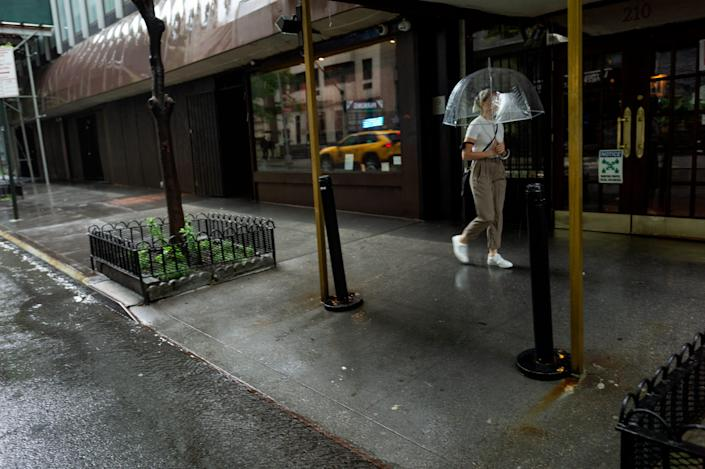 A view of a sidewalk with a woman, holding an umbrella, walking by.
