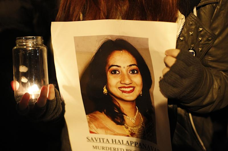FILE - This Thursday Nov. 15, 2012 file photo shows a woman holding a picture of Savita Halappanava during a candlelit vigil outside Belfast City Hall, Northern Ireland, for Savita Halappanavar, the 31-year old Indian woman who was 17-weeks pregnant when she died of blood poisoning after suffering a miscarriage in Galway, Ireland, on 28 October. Ireland appeared on course to legalize abortion in extremely restricted circumstances as lawmakers voted Tuesday July 2, 2013 to support a bill that would permit pregnancies to be terminated when deemed necessary to save the woman's life. (AP Photo/Peter Morrison, File)