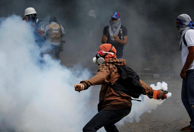 <p>Opposition supporters clash with security forces during protests against President Nicolas Maduro in Caracas, Venezuela, May 4, 2017. (Carlos Garcia Rawlins/Reuters) </p>