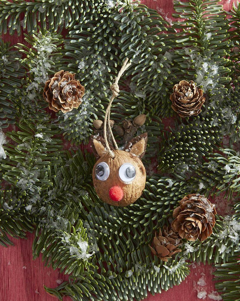 """<p>Greet Santa with this fresh and friendly faced Rudolph ornament. His shiny red nose will lead Santa right to the cookies you left under the tree.</p><p><strong>To make:</strong> Drill a small hole toward the top of a half of a walnut shell. Attach mini googly eyes, a mini red pom pom, and brown felt ears with hot glue. Thread a piece of twine through the hole and knot.</p><p><a class=""""link rapid-noclick-resp"""" href=""""https://www.amazon.com/NUTS-U-S-California-Chandler-Resealable/dp/B07M8PJ37J/ref=sr_1_1?tag=syn-yahoo-20&ascsubtag=%5Bartid%7C10050.g.1070%5Bsrc%7Cyahoo-us"""" rel=""""nofollow noopener"""" target=""""_blank"""" data-ylk=""""slk:SHOP WALNUTS"""">SHOP WALNUTS</a></p>"""