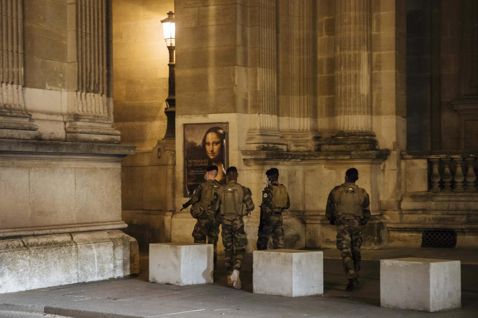 Military patrol near the Louvre museum during curfew in Paris, Saturday, Oct. 17, 2020. French restaurants, cinemas and theaters are trying to figure out how to survive a new curfew aimed at stemming the flow of record new coronavirus infections. The monthlong curfew came into effect Friday at midnight, and France is deploying 12,000 extra police to enforce it. (AP Photo/Lewis Joly)