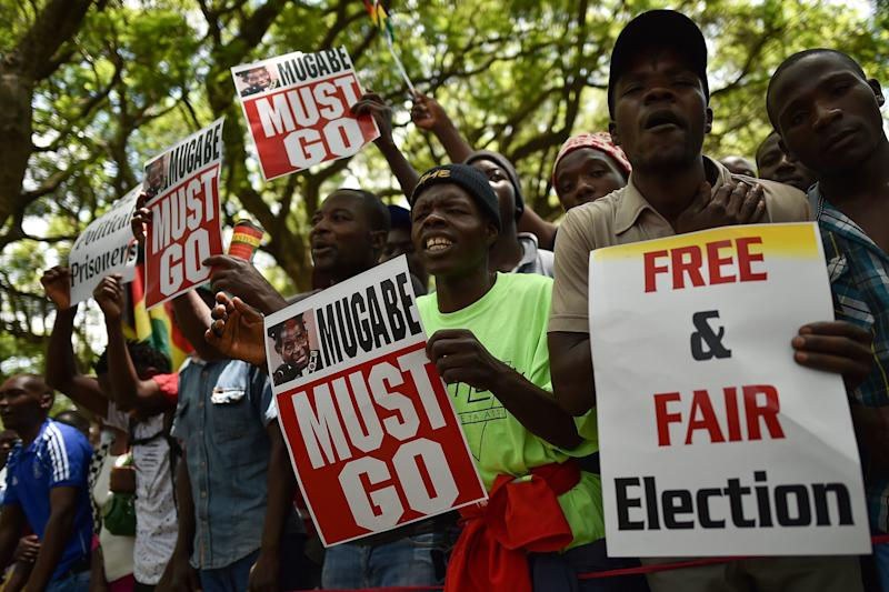 Protesters hold signs during a gathering in Zimbabwe's capital of Harare on Nov. 21, 2017, calling for Mugabe to step down.