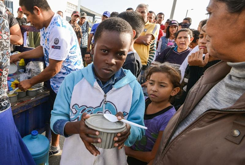 Venezuelan nationals receive food from religious volunteers while they wait for authorization to enter Peru