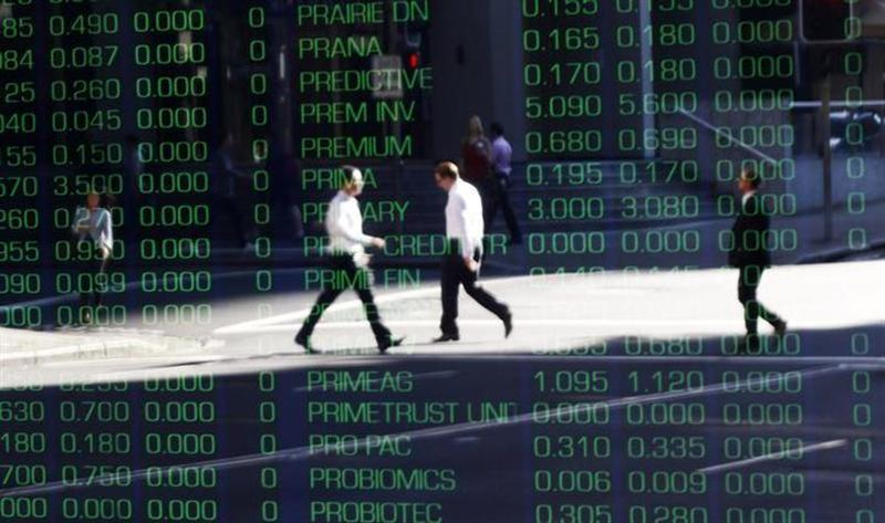 Office workers are reflected on a screen displaying share prices as they walk past the Australian Securities Exchange building in central Sydney September 23, 2011. REUTERS/Daniel Munoz/Files