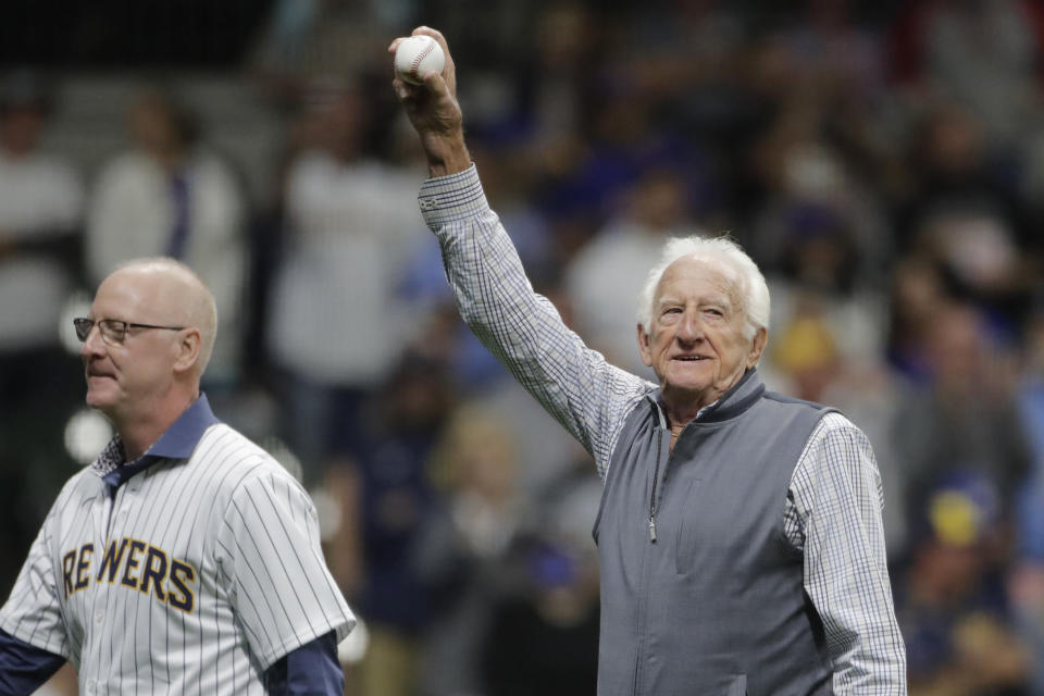 Broadcaster Bob Uecker, right, waves to the crowd after throwing out the ceremonial first pitch before a baseball game between the Milwaukee Brewers and the New York Mets Saturday, Sept. 25, 2021, in Milwaukee. (AP Photo/Aaron Gash)