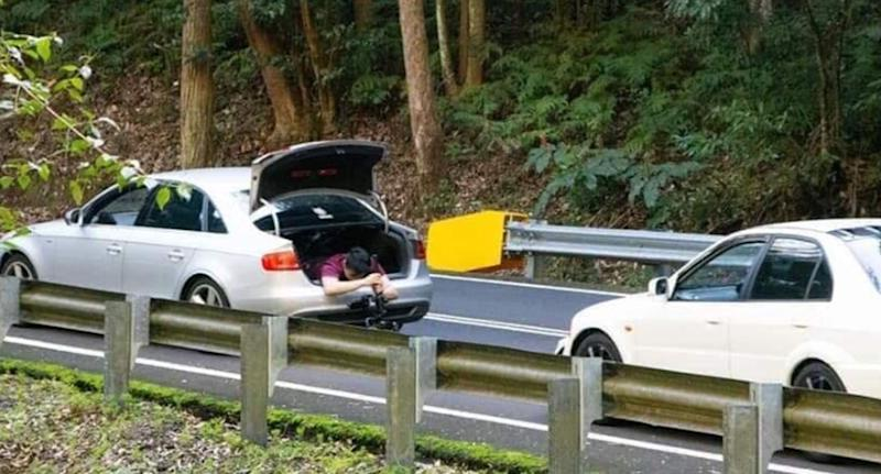 Pictured is the man holding a camera while hanging out of an Audi's boot in the Royal National Park near Sydney.