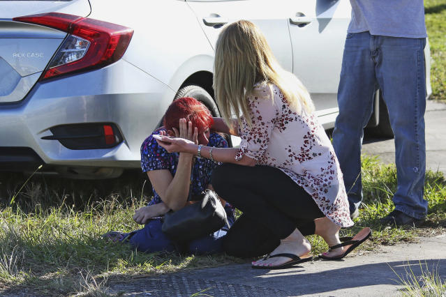 <p>A woman consoles another as parents wait for news regarding a shooting at Marjory Stoneman Douglas High School in Parkland, Fla., on Feb. 14, 2018. (Photo: Joel Auerbach/AP) </p>