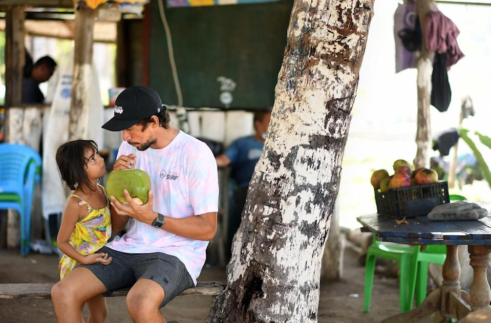 Bryan Perez sips on a coconut with family at his father's refreshment stand
