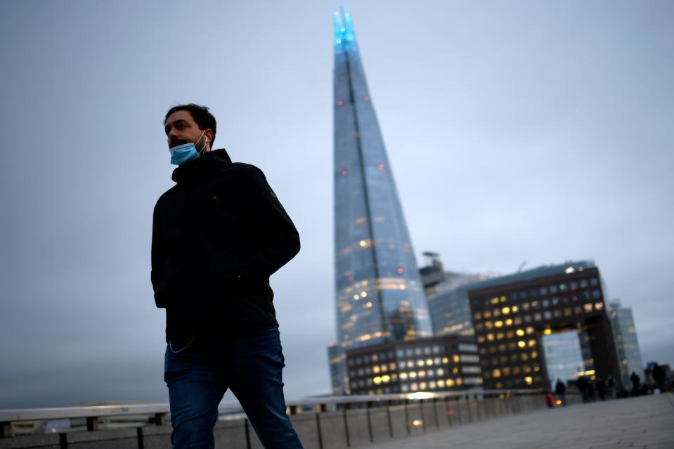 A pedestrian crosses London Bridge with the Shard tower in the background. Photo: Tolga Akmen/AFP via Getty