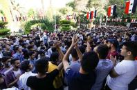 Students gesture as they wait outside a polling station before the polls open for the presidential elections, in Damascus
