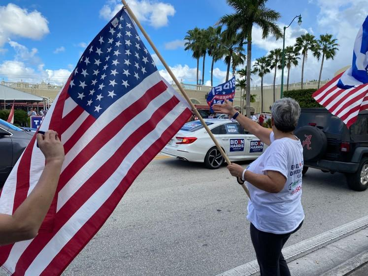 Lourdes Naranjo, waves a American flag during a Biden caravan, October 18, in Miami, Fla. A group of Trump supporters gathered outside of Versailles and both sides shouted at one another.