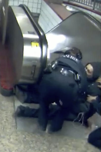 In this Feb. 28, 2020 image from video provided by the Civilian Office of Police Accountability, police officers tend to Ariel Roman after he was shot by police in a subway station in Chicago. Extended security and body-cam video released Tuesday, April 28, 2020 shows Chicago police shooting the unarmed short-order cook at the foot of a subway escalator and then again with his back turned to officers after they tried to stop him for violating a city ordinance by walking from one train car to another. (Chicago Transit Authority, Civilian Office of Police Accountability via AP)