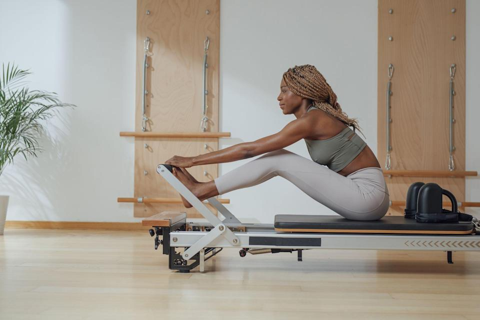 """<p>If your fitness goals include building lean muscle, improving flexibility, and strengthening your core, <a href=""""https://www.prevention.com/fitness/a30432062/what-is-pilates/"""" rel=""""nofollow noopener"""" target=""""_blank"""" data-ylk=""""slk:Pilates"""" class=""""link rapid-noclick-resp"""">Pilates</a> may be the perfect exercise for you. You could roll out a mat to <a href=""""https://www.prevention.com/fitness/workouts/g30470149/pilates-for-beginners/"""" rel=""""nofollow noopener"""" target=""""_blank"""" data-ylk=""""slk:get started"""" class=""""link rapid-noclick-resp"""">get started</a>. But if you're more experienced (and miss attending studio sessions due to the pandemic), you might want to invest in a Pilates reformer for your home.</p><p>Recent research has shown that regular reformer exercise is associated with <a href=""""https://pubmed.ncbi.nlm.nih.gov/28167194/"""" rel=""""nofollow noopener"""" target=""""_blank"""" data-ylk=""""slk:greater shoulder"""" class=""""link rapid-noclick-resp"""">greater shoulder</a> and lower back strength, plus a <a href=""""https://pubmed.ncbi.nlm.nih.gov/30368346/"""" rel=""""nofollow noopener"""" target=""""_blank"""" data-ylk=""""slk:decreased chance"""" class=""""link rapid-noclick-resp"""">decreased chance</a> of falling in people over 65, proving that the machines are worth the investment. Here's what to look for in a Pilates reformer, plus plenty of options at every price point—and experience level—to add to your home fitness studio.</p><h2 class=""""body-h2"""">What is a Pilates reformer?</h2><p>Invented by Joseph Pilates, a Pilates reformer is an apparatus that creates resistance to work every muscle in your body. It consists of a carriage with a sliding platform held back by adjustable springs, explains <a href=""""https://www.nexapilates.com/trainers"""" rel=""""nofollow noopener"""" target=""""_blank"""" data-ylk=""""slk:Anna Clark"""" class=""""link rapid-noclick-resp"""">Anna Clark</a>, trainer and co-owner of Nexa Pilates and Fitness in New York. The springs offer muscle-shaking resistance while facilitating full-body stretching.</p><p>""""Adding Pil"""