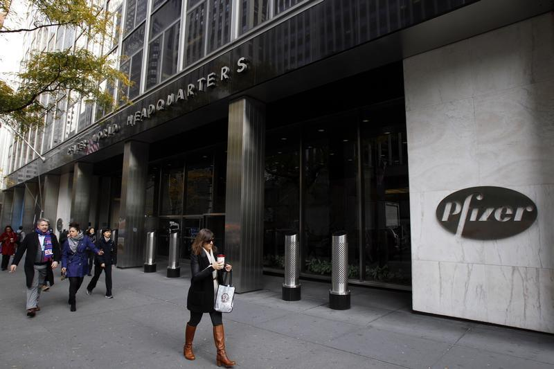 Pedestrians walk past the world headquarters of Pfizer in New York