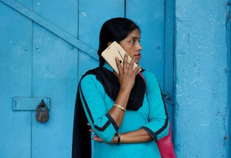 FILE PHOTO: A woman talks on her mobile phone on a pavement in Kolkata