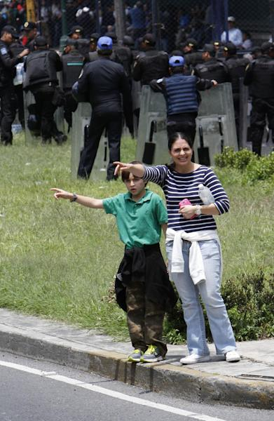 A woman and a child try to hail a cab as riot police, behind, keep protesters back near the Los Pinos presidential residence in Mexico City, Wednesday, Aug. 28, 2013. A week of protests by striking teachers have so snarled this metropolis million that the city has launched an app to warn drivers of street blockades and canceled two weekend first-division soccer games. Taxi drivers are so desperate they are refusing fares to certain frequently blocked parts of the city. (AP Photo/Marco Ugarte)