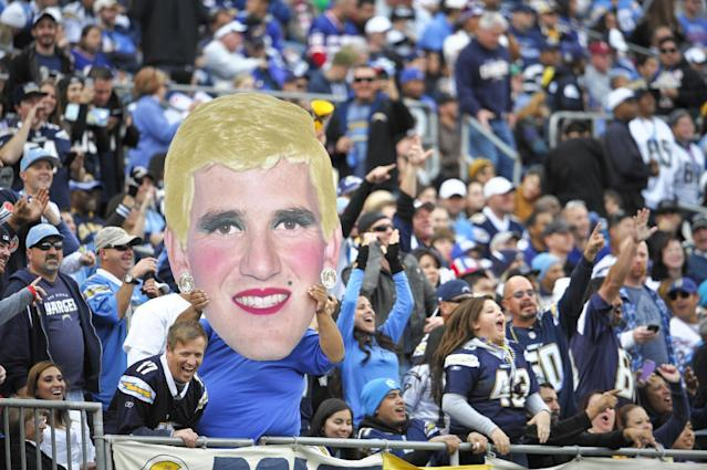 San Diego Chargers fans hold an altered image of New York Giants quarterback Eli Manning during an NFL football game on Sunday, Dec. 8, 2013, in San Diego. (AP Photo/Denis Poroy)