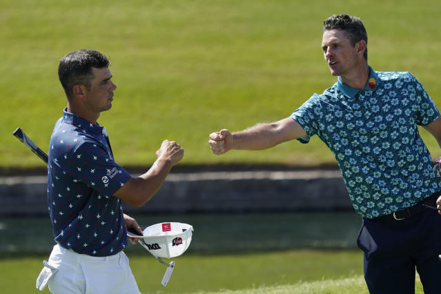 Gary Woodland, left, and Justin Rose, of England, nearly touch fists on the 18th green following the third round of the Charles Schwab Challenge golf tournament at the Colonial Country Club in Fort Worth, Texas, Saturday, June 13, 2020. (AP Photo/David J. Phillip)