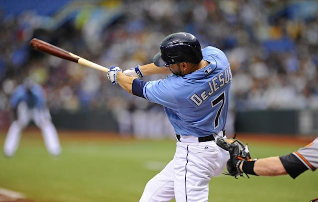 Tampa Bay Rays' David DeJesus follows through as he hits a home run against the Baltimore Orioles during the first inning of a baseball game Sunday, Sept. 22, 2013, in St. Petersburg, Fla. (AP Photo/Brian Blanco)
