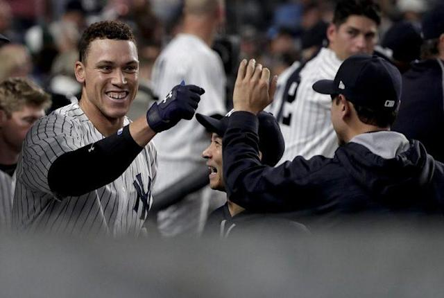 Yankees slugger Aaron Judge (left) is congratulated after hitting one of his two home runs on Friday night. (AP)