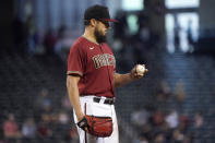 Arizona Diamondbacks starting pitcher Caleb Smith looks at the baseball after giving up a run against the Milwaukee Brewers during the XXX inning of a baseball game, Wednesday, June 23, 2021, in Phoenix. (AP Photo/Matt York)