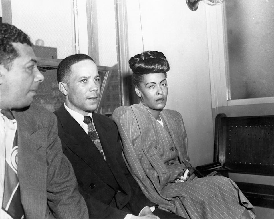 Billie Holiday wearing a skirt suit near a court room