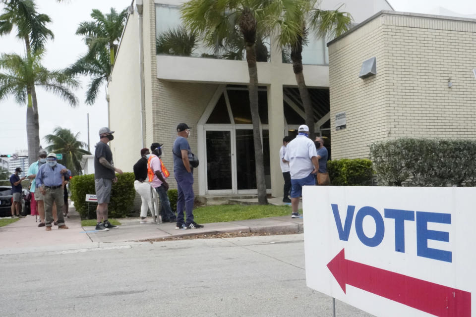 FILE - People wait in line to vote outside of an early voting site in Miami Beach, Fla. on Oct. 20, 2020. Television networks are adding experts in election law to their election night coverage teams so they're prepared to explain legal challenges or irregularities that come up during the vote. (AP Photo/Wilfredo Lee, File)