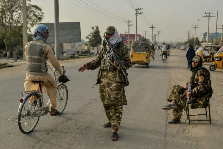 Taliban fighters check commuters in the Afghan city of Kunduz, scene of a deadly attack on a Shiite mosque claimed by the local branch of the Islamic State group last week (AFP/Hoshang Hashimi)