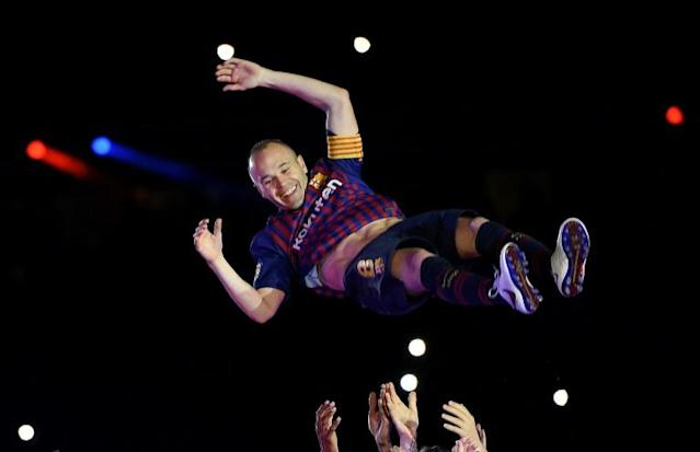 Japan bound: Andres Iniesta is thrown in the air by Barcelona teammates at his last match for the club at the weekend