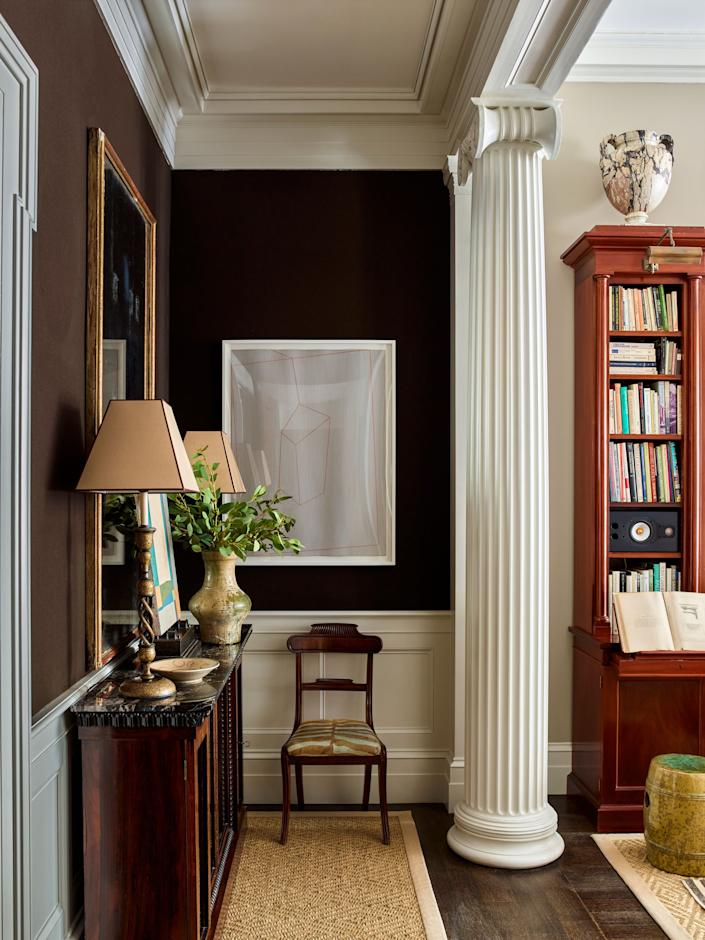 """<div class=""""caption""""> A nook off the living room features a Regency mahogany cabinet from <a href=""""https://www.1stdibs.com/dealers/niall-smith-antiques"""" rel=""""nofollow noopener"""" target=""""_blank"""" data-ylk=""""slk:Niall Smith Antiques"""" class=""""link rapid-noclick-resp"""">Niall Smith Antiques</a>, a mahogany side chair from <a href=""""https://sutterantiques.com/"""" rel=""""nofollow noopener"""" target=""""_blank"""" data-ylk=""""slk:Sutter Antiques"""" class=""""link rapid-noclick-resp"""">Sutter Antiques</a>, and original artwork by Maine artist Corey Daniels. The Kashmiri lamps are from <a href=""""https://www.robertkime.com/"""" rel=""""nofollow noopener"""" target=""""_blank"""" data-ylk=""""slk:Robert Kime"""" class=""""link rapid-noclick-resp"""">Robert Kime</a>, and the marble urn was acquired at an auction at <a href=""""https://www.christies.com/"""" rel=""""nofollow noopener"""" target=""""_blank"""" data-ylk=""""slk:Christie's"""" class=""""link rapid-noclick-resp"""">Christie's</a>. </div>"""