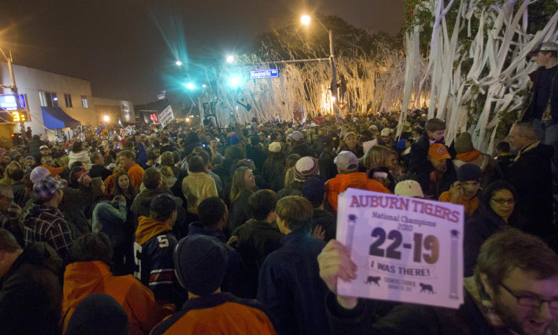Thousands of Auburn Tiger fans gather to roll Toomer's Corner in Auburn, Ala., Monday, Jan. 10, 2011 following a 22-19 Auburn win over the Oregon Ducks in the BCS championship game.  (AP Photo/Dave Martin)