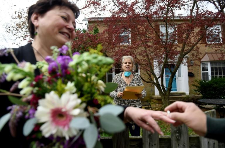 A newly married couple exchanges wedding rings in front of the home of a Virginia state marriage officiant who performs the ceremony while maintaining social distance due to the Coronavirus outbreak on April 1, 2020 in Arlington, Virginia. (AFP Photo/Olivier DOULIERY)