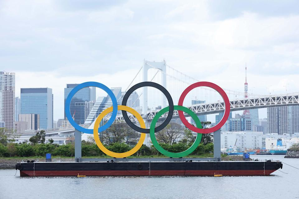 The Olympic rings sculpture, Rainbow Bridge and the Tokyo Tower are pictured from Odaiba on April 6, 2021, in Tokyo.