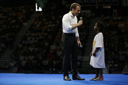 Emmanuel Macron, head of the political movement En Marche ! (Onwards !) and 2017 presidential candidate of the French centre-right speaks with a young boy at a meeting at Saint Denis