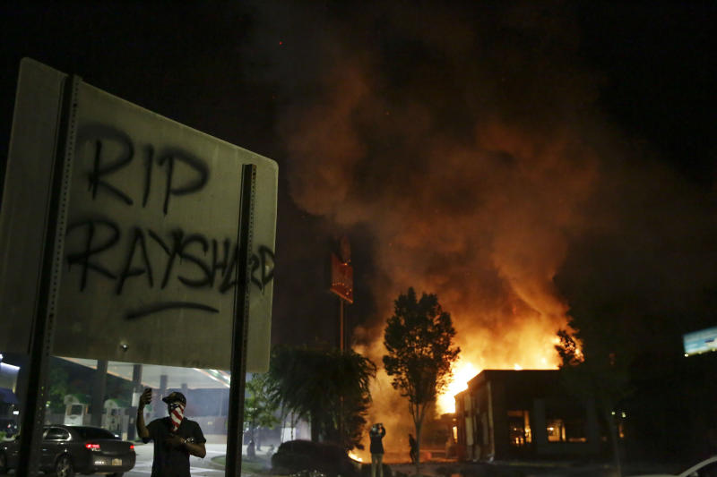 """In this Saturday, June 13, 2020, file photo, """"RIP Rayshard"""" is spray-painted on a sign as flames engulf a Wendy's restaurant during protests in Atlanta. The restaurant was where Rayshard Brooks was shot and killed by police the previous evening following a struggle in the restaurant's drive-thru line. The deadly police shooting soon after the city erupted in fiery demonstrations protesting police brutality have cast a harsh spotlight on cracks in Atlanta's reputation for Black prosperity in politics and business. (AP Photo/Brynn Anderson, File)"""