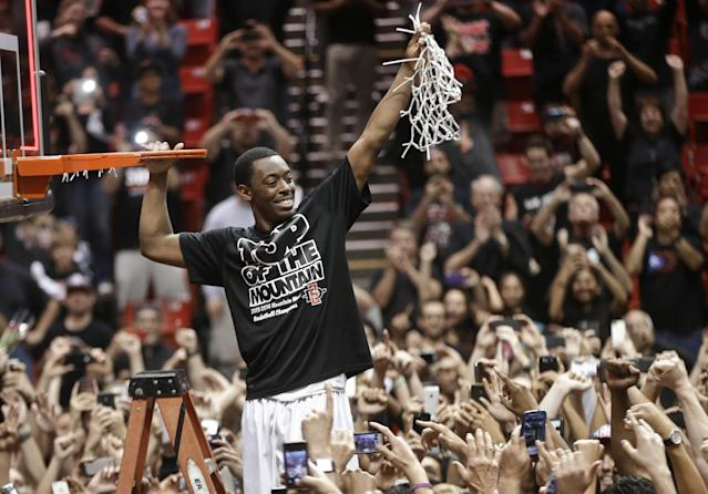 San Diego State's Xavier Thames holds up a cut net after San Diego State defeated New Mexico 51-48 to win the Mountain West Conference title, in an NCAA college basketball game Saturday, March 8, 2014, in San Diego. (AP Photo/Lenny Ignelzi)